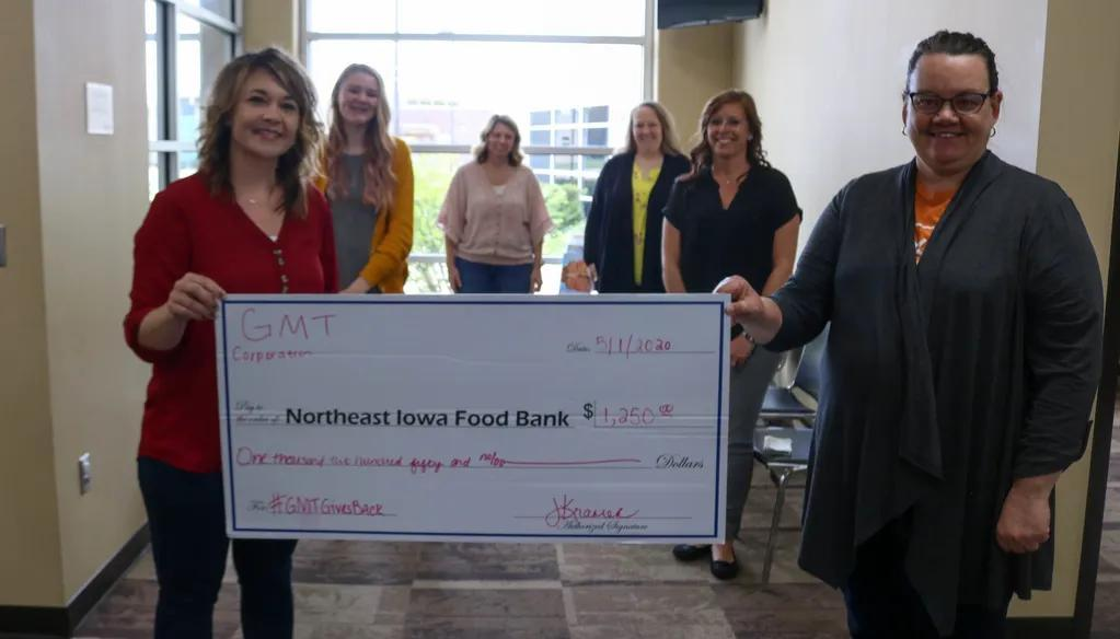 GMT Corporation Employees Holding Donation Check for Northeast Iowa Food Bank
